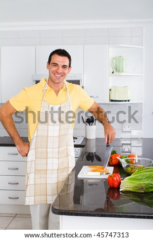 young happy bachelor in kitchen cooking food - stock photo
