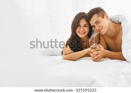 Young happy beautiful couple lying in bed and smiling at camera. Love and relationships concept.