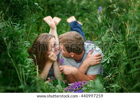 Young happy beautiful couple man and woman lying outdoors on green grass - stock photo