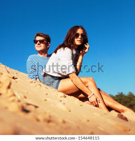 Young happy beautiful fashion couple having fun in summer sitting in sand behind blue sky.  - stock photo