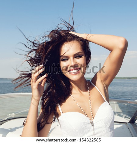 Young happy beautiful woman have fun on the luxury boat in open sea in summer. Caucasian female model. Outdoors, lifestyle. - stock photo