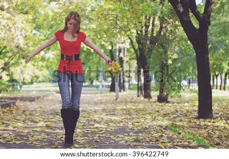 young happy beautiful woman in red with yellow maple leaves - stock photo