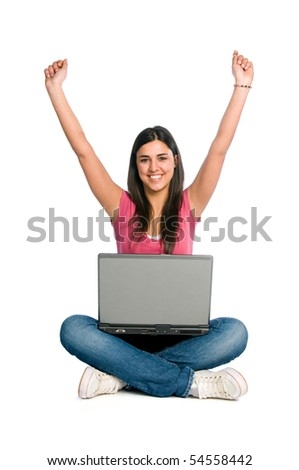 Young happy beautiful woman raised the arms to celebrate in front of her laptop isolated on white background
