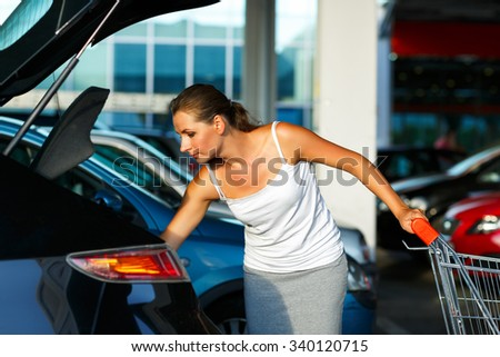 Young happy beautiful woman shifts the purchase from shopping cart in the trunk of a car on the parking - stock photo
