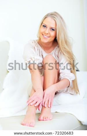 Young happy beautiful woman sitting on the bed at home and touching her legs