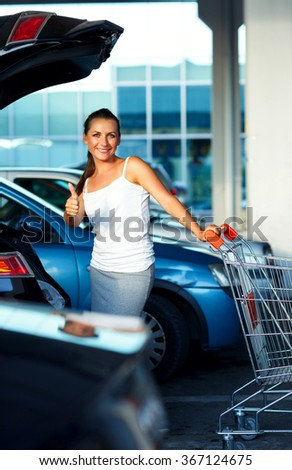 Young happy beautiful woman standing with shopping cart and thumb up near the car on the parking