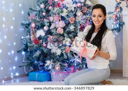 Young happy beautiful woman with gift box sits near Christmas tree in the room of the house. Merry Christmas and New Year. - stock photo