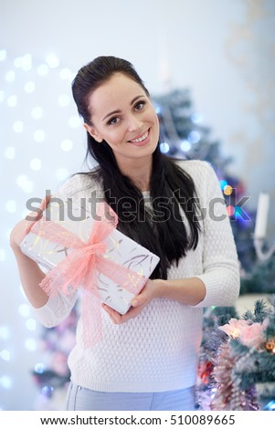 Young happy beautiful woman with gift boxes stands near Christmas tree in the room of the house.  Merry Christmas and New Year.
