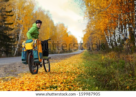 Young happy bicycle tourist with his loaded bike standing on an autumn road in a sunny day