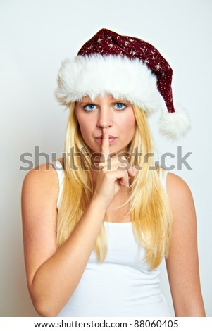 young happy blond christmas woman with a secret - stock photo