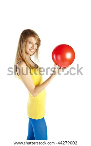 Young happy blond woman standing on tiptoe and holding red ball