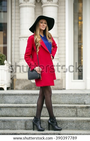 Young happy blonde woman in red coat walks on the spring street in Moscow
