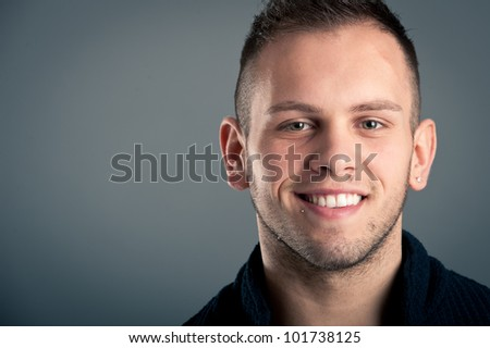 Young happy boy close up portrait against grey background with room for text. - stock photo