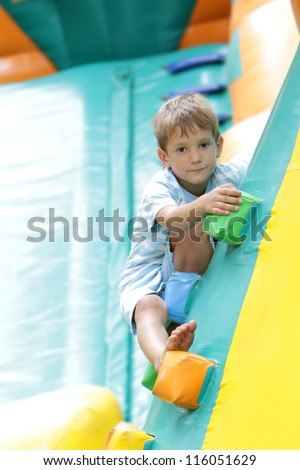 young happy boy having fun on trampoline outdoors - stock photo
