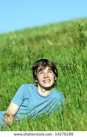 Young happy boy lying on the grass - stock photo