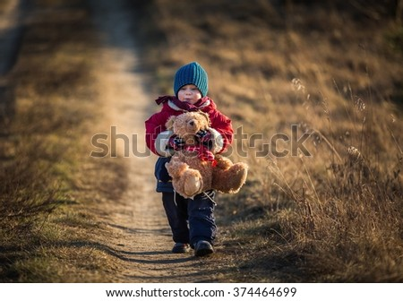 Young happy boy playing with his teddy bear toy outdoor in beautiful rural landscape in golden light at spring. Happy childhood spent in the countryside. - stock photo