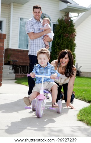 Young happy boy riding tricycle with family watching - stock photo