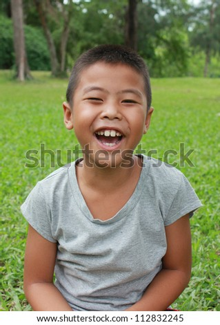 Young happy boy sitting in the park. - stock photo