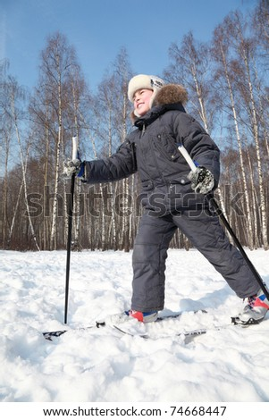 Young happy boy skates on cross-country skis with poles inside winter forest at sunny day - stock photo
