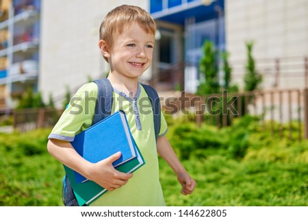 Young happy boy with books in front of school building - stock photo