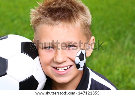 Young happy boy with painted face and soccer ball. - stock photo