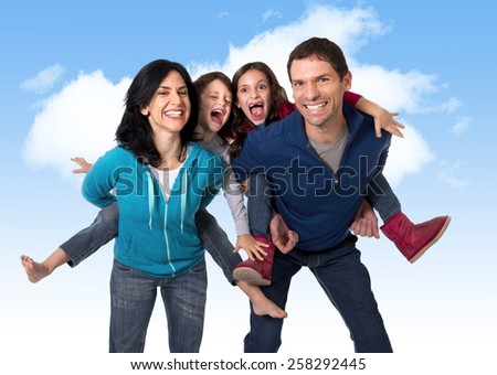 young happy Brazilian mother and father playing with little son and daughter having fun all together outdoors on a blue sky with clouds in family love and new generation concept  - stock photo