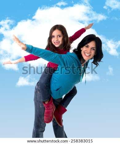 young happy Brazilian mother carrying on her back  little daughter as airplane flying having fun together playing in freedom concept on blue sky with clouds background - stock photo