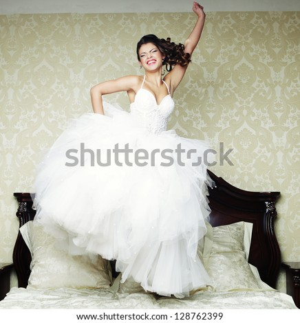 Young happy bride jump on bed. - stock photo