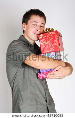 young happy brunette man holding many gifts and smiling - stock photo