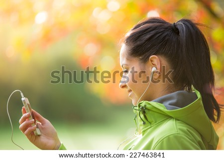 Young happy brunette woman listening to music in autumn park. - stock photo