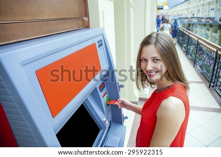 Young happy brunette woman withdrawing money from credit card at ATM  - stock photo