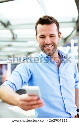 Young happy buisnessman looking at smartphone outside the office - stock photo