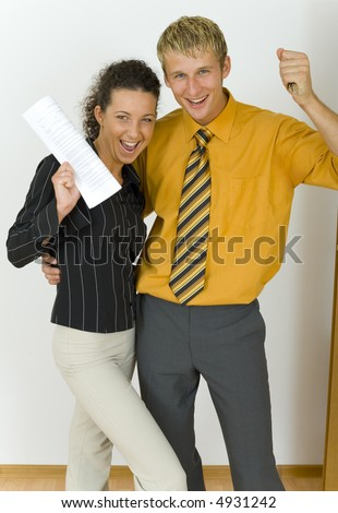 Young, happy business couple. Man is holding keys, woman is holding  some kind of contract. Looking at camera, front view - stock photo