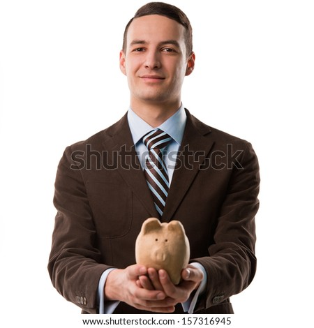 Young happy business man holding piggybank over white background - stock photo