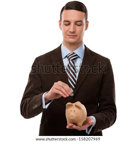 Young happy business man putting money in the piggybank over white background - stock photo