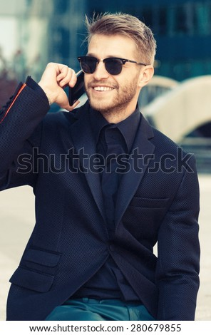 Young happy business man using his smart phone in front of his work place - stock photo
