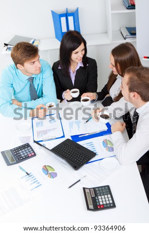 Young happy business people, drinking coffee and talking, break, smiling, working on project in team together, men and women discussing, businesspeople meeting sitting at desk office, above top view - stock photo