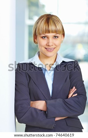 Young happy business woman standing casually with hands folded