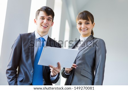 Young happy businessman and businesswoman people discussing project - stock photo