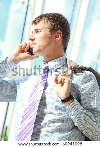 Young happy businessman calling on mobile phone, outdoor, smiling