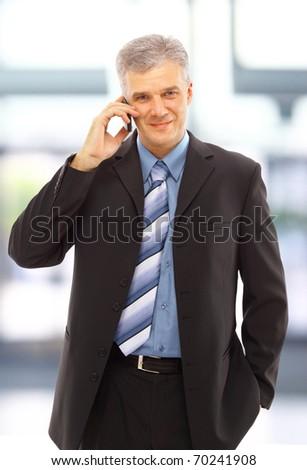 Young happy businessman calling on mobile phone, outdoor, smiling - stock photo