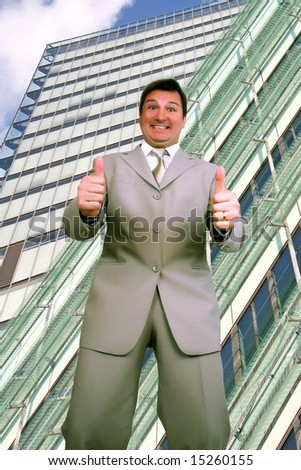 Young happy businessman in front of a modern office building - stock photo
