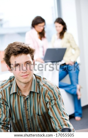 Young happy businessman looking at camera, smiling while business team working in background.