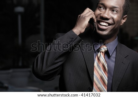 Young happy businessman on a talking on a cellular telephone