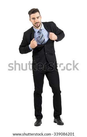 Young happy businessman pulling and stretching his suit jacket smiling at camera. Full body length portrait isolated over white studio background.  - stock photo