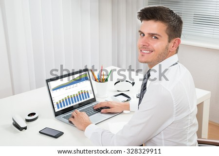 Young Happy Businessman Working With Graph On Laptop In Office