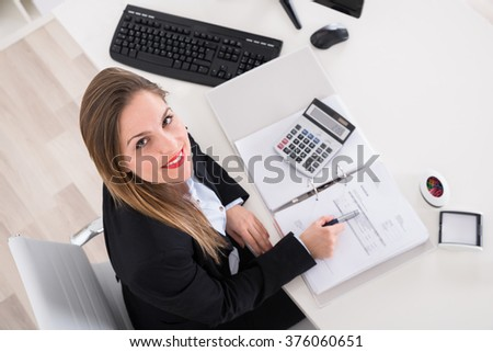 Young Happy Businesswoman Calculating Tax At Office - stock photo