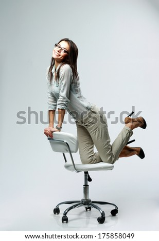 Young happy businesswoman having fun on office chair on gray background - stock photo