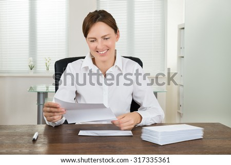 Young Happy Businesswoman Holding Document With Stack Of Envelopes At Desk In Office - stock photo