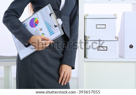 Young happy businesswoman in office holding a folder - stock photo